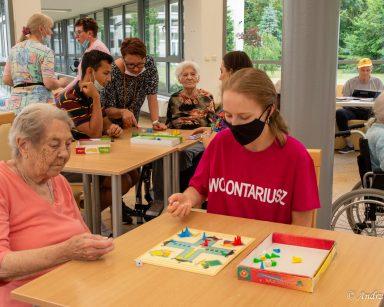 Ogród zimowy. Przy stolikach seniorzy, wolontariusze i pracownicy grają w gry planszowe.