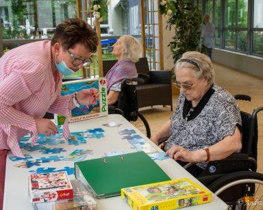Kierowniczka Mariola Ludwicka i seniorka przy stole w ogrodzie zimowym. Wspólnie układają puzzle.