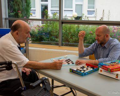 Przy oknie siedzi senior i kierownik Arkadiusz Wanat. Grają ze sobą w warcaby.