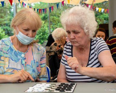 Seniorka i terapeutka Ewa Rodziewicz nachylają się nad stołem. Na blacie gra w warcaby. W tle inni seniorzy i pracownicy.