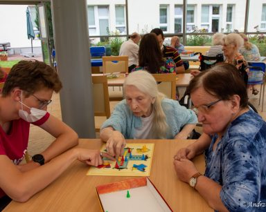 Przy stoliku dwie seniorki i wolontariuszka. Wspólnie grają w