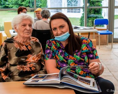 Przy stoliku w ogrodzie zimowym seniorka i fizjoterapeutka Paulina Winczura. Oglądają album.