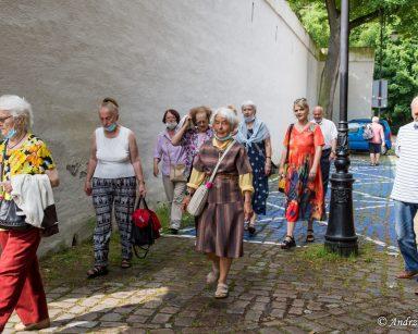 Terapeutka Beata Gadomska i seniorzy idą na spacer po Parku Oliwskim.