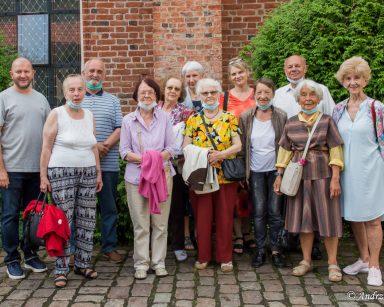 Seniorzy, kierownik Arkadiusz Wanat, terapeutka Beata Gadomska pozują do wspólnego zdjęcia. W tle budynek z czerwonej cegły.