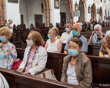 Wnętrze kościoła. Seniorzy siedzą w drewnianych ławkach. Za nimi inni zwiedzający.