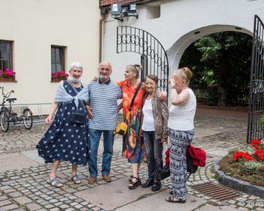 Seniorzy, terapeutka Beata Gadomska pozują do wspólnego zdjęcia na brukowanym placu.
