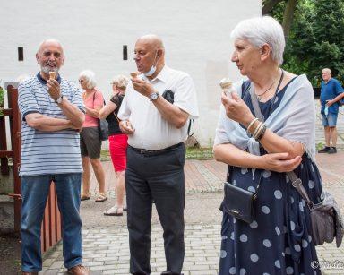 Seniorzy jedzą lody w trakcie spaceru.