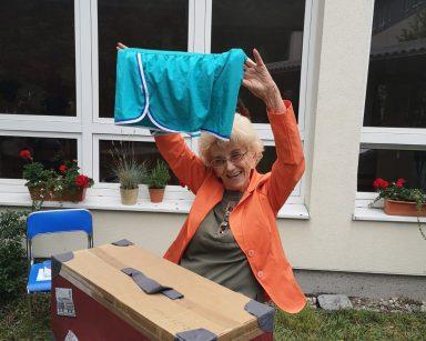 Na stoliku w ogrodzie walizka. Seniorka wyciąga z niej ortalionowe szorty. Unosi je wysoko i się śmieje.