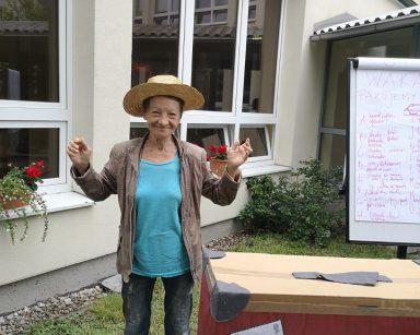 Na trawie stoi uśmiechnięta seniorka. Na głowie ma słomkowy kapelusz. Przed nią, na stoliku walizka.