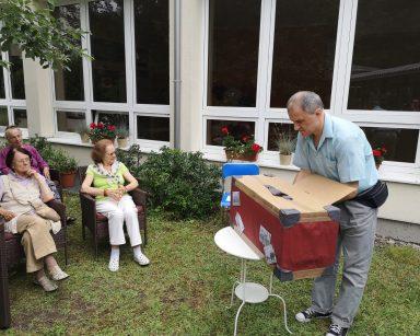 Na stoliku w ogrodzie walizka. Senior nachyla się nad nią i próbuje wyciągnąć z niej jakiś przedmiot. Obok inni seniorzy.