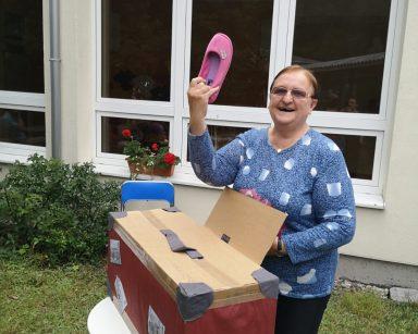 Na stoliku w ogrodzie walizka. Seniorka wyciąga z niej różowy pantofel. Unosi go wysoko i się śmieje.