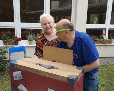 Na stoliku w ogrodzie walizka. Dwoje roześmianych seniorów próbuje wyciągnąć z niej jakiś przedmiot.