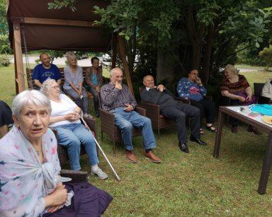 W cieniu drzew, na rattanowych fotelach i na drewnianej huśtawce siedzą seniorzy.