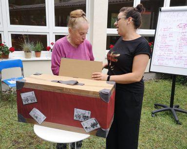 W ogrodzie terapeutka Małgosia Jancelewicz i seniorka. Stoją przy walizce i rozmawiają.