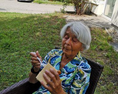 W zacienionym ogrodzie, na rattanowym fotelu siedzi seniorka. W rękach trzyma wafelek z lodem i łyżeczkę.