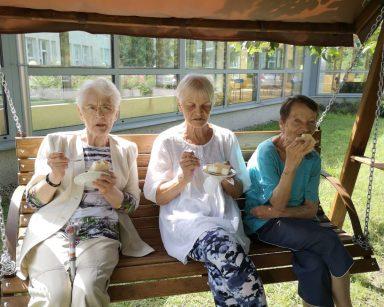 W ogrodzie drewniana ławka z baldachimem. Na niej siedzą trzy seniorki. Jedzą lody.
