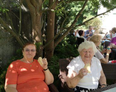 Przy drzewie, w cieniu dwie seniorki. Siedzą przy stoliku i jedzą lody. W tle inni seniorzy w trakcie deseru.