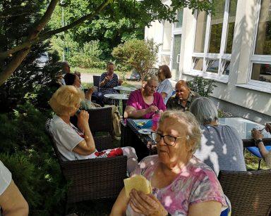 W ogrodzie, w cieniu drzew seniorzy. Siedzą przy stolikach i jedzą lody. Rozmawiają.