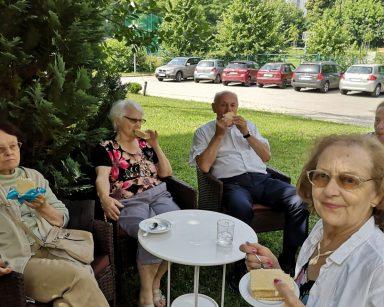 W ogrodzie, w cieniu drzew seniorzy. Siedzą przy stolikach i jedzą lody.