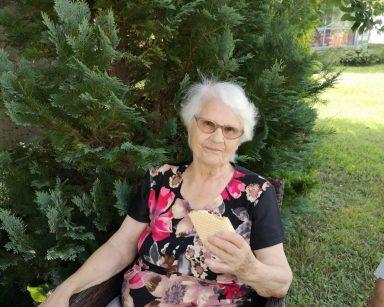 Seniorka siedzi w rattanowym fotelu. Uśmiecha się i je loda. W tle widać zielony ogród.