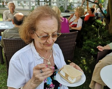 Przy drzewie, w cieniu seniorka. W dłoniach trzyma łyżeczkę i talerzyk z lodem. W tle inni seniorzy w trakcie deseru.