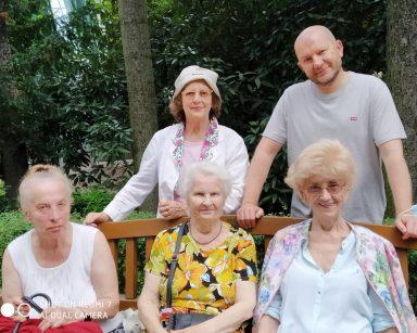 Trzy seniorki na ławce w Parku Oliwskim. Za nimi stoją seniorka i kierownik Arkadiusz Wanat.