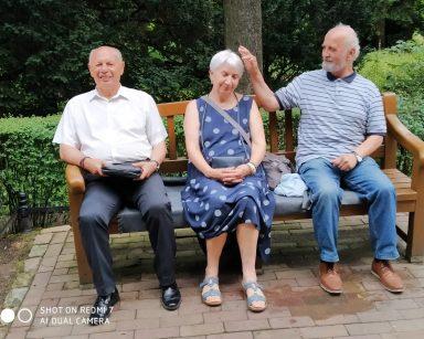 Troje seniorów na ławce w Parku Oliwskim.