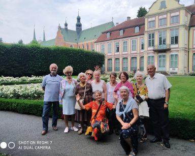 Seniorzy, terapeutka Beata Gadomska pozują do wspólnego zdjęcia. Za nimi trawnik, kwitnące kwiaty, budynki.