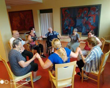 Agnieszka Sut, koordynatorka Edyta Życzyńska i seniorzy na zajęciach Biodanzy. Siedzą w kółku i trzymają się za ręce.