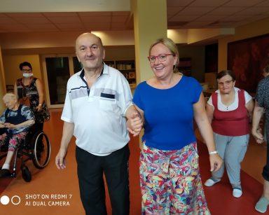 Instruktorka Agnieszka Sut pod rękę z seniorem. Za nimi, w parach inni uczestnicy Biodanzy.
