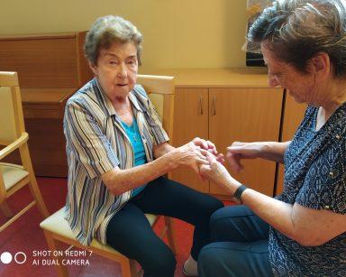 Seniorki w trakcie Biodanzy. Siedzą na krzesłach, trzymają się za ręce.