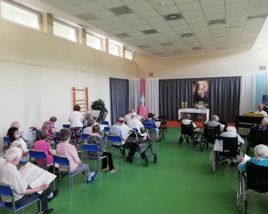 Na sali seniorzy siedzą w rzędach. W rękach trzymają śpiewniki. Przed nimi kierownik Arkadiusz Wanat. Siedzi przy pianinie.