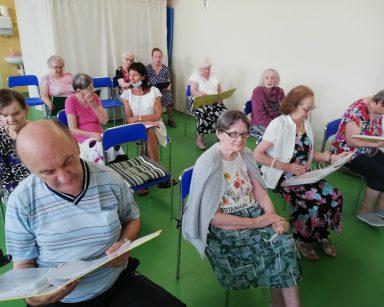 Na sali seniorzy siedzą w rzędach. W rękach trzymają śpiewniki. Śpiewają. Wśród nich terapeutka Anna Rzepczyńska.