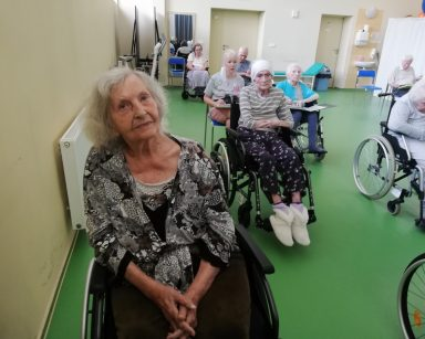 Na sali seniorzy siedzą w rzędach. Część z nich trzyma w rękach śpiewniki. Śpiewają.