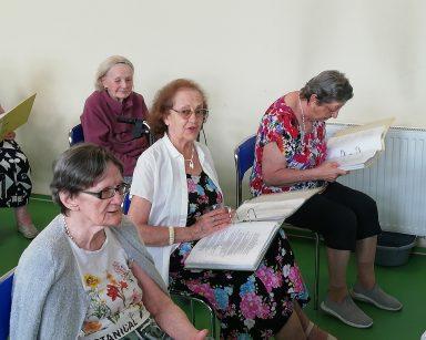 Na sali seniorzy siedzą w rzędach. W rękach trzymają śpiewniki. Śpiewają.
