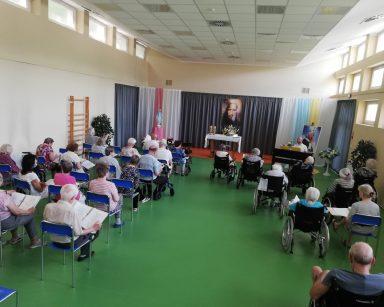 Na sali seniorzy siedzą w rzędach. W rękach trzymają śpiewniki. Przed nimi kierownik Arkadiusz Wanat. Gra na pianinie.