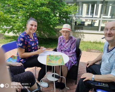 Na patio, przy stoliku fizjoterapeutka Martyna Józefczyk i seniorzy. Na blacie rozłożona gra planszowa z pionkami.