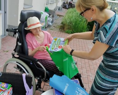 Na patio dyrektorka Agnieszka Cysewska i seniorka. Wspólnie rozpakowują zieloną torbę. Obok na stoliku rozpakowane gry.