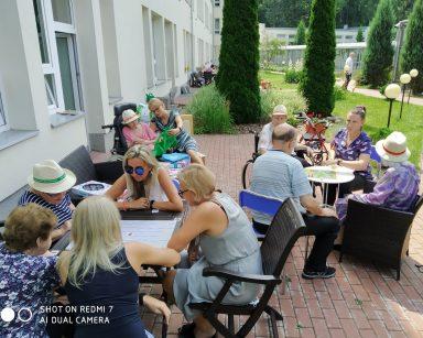 Na patio w ogrodzie dyrektorka Agnieszka Cysewska, seniorzy i pracownicy. Grają przy stolikach w gry planszowe.