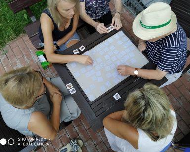 Widok z góry. Przy stoliku pracownicy i seniorki. Grają w grę planszową, która ćwiczy pamięć.