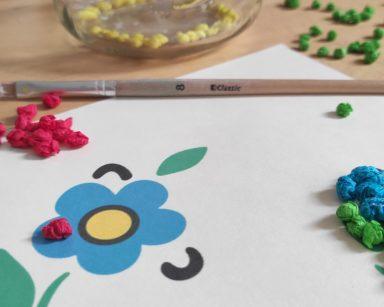 Kartka z wzorem kaszubskim. Jeden z kwiatów jest już wyklejony kulkami z bibuły. Obok pędzelek, kolorowe kulki z bibuły.