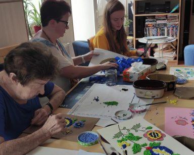 Seniorka, koordynatorka wolontariatu Edyta Życzyńska, pracownica Ania Dudziak przy stole. Przygotowują bibułę, wyklejają obrazki.