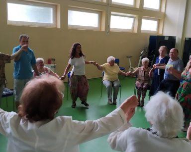 Jasna sala. Agnieszka Sut, wolontariuszki i seniorzy. Biorą udział w zajęciach Biodanzy. Śmieją się, tańczą, trzymają się za ręce.