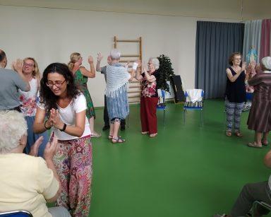 Jasna sala. Agnieszka Sut, wolontariuszki i seniorzy. Biorą udział w zajęciach Biodanzy. Tańczą i ćwiczą w parach.