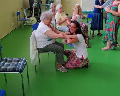 Jasna sala. Wolontariuszki i seniorzy biorą udział w zajęciach Biodanzy. Śmieją się, tańczą, trzymają się za ręce.