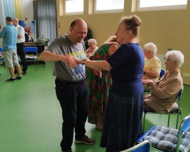 Jasna sala. Seniorzy biorą udział w zajęciach Biodanzy. Śmieją się, tańczą, trzymają się za ręce.