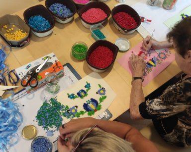 Przy stole pracują seniorka i szefowa kadr Anna Foras-Misiewicz. Na blacie kolorowe wstążki, kuleczki z bibuły.