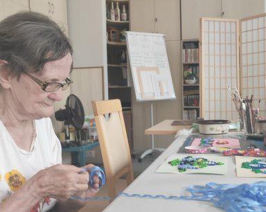 Seniorka zwija niebieska wstążkę. Na blacie inspirowane haftem kaszubskim kolorowe obrazki, papierowe lalki.