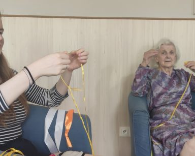 Seniorka i pracownica Ania Dudziak siedzą w fotelach. Zwijają żółte wstążki.