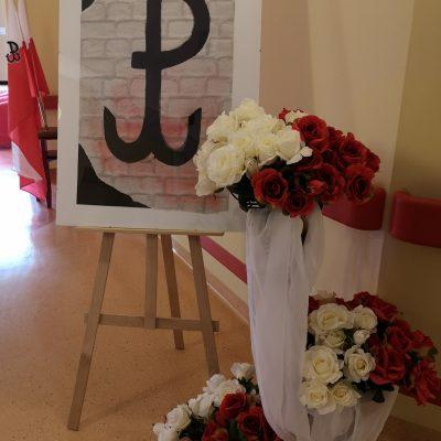 Dekoracja. Plakat z symbolem Polski Walczącej. Obok bukiety białych i czerwonych róż ozdobione białym tiulem.